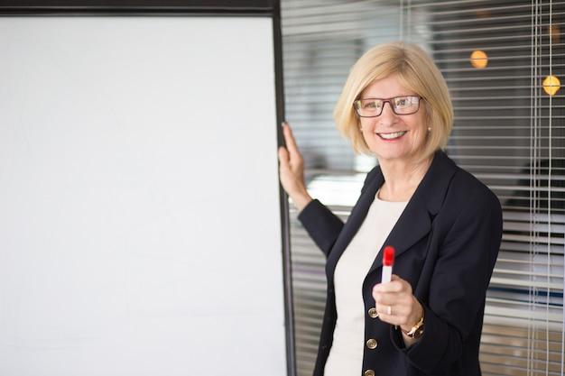 Smiling senior business lady addressing audience