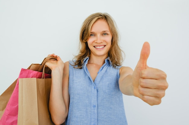 Smiling woman holding bags e mostrando thumb up