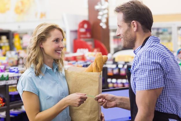 Smilingm mulher na caixa registradora, pagando com cartão de crédito
