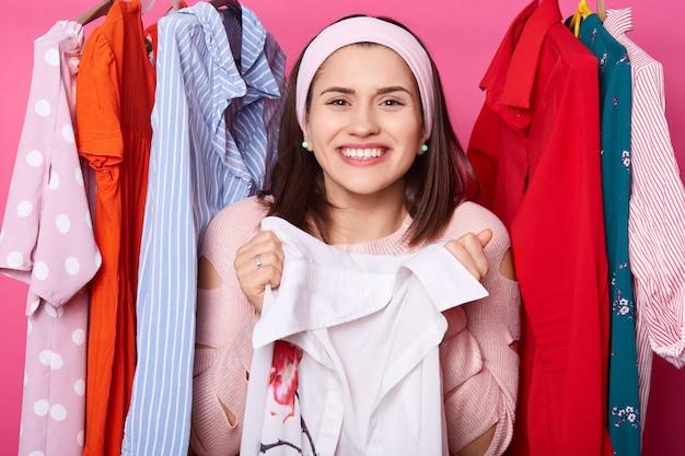Smilling menina de cabelos castanho veste camisa rosa, detém blusa branca. lady fica perto de muitos cabides com roupas novas. garota feliz vai às compras. mulheres com pulseira e brincos finalmente encontram presentes.