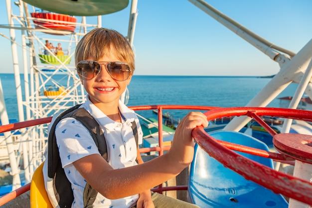 Smilling menino animado em copos, apreciando a vista da roda gigante no parque de diversões