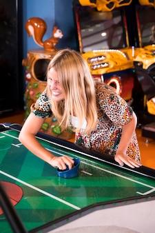 Smilling mulher jogando air hockey