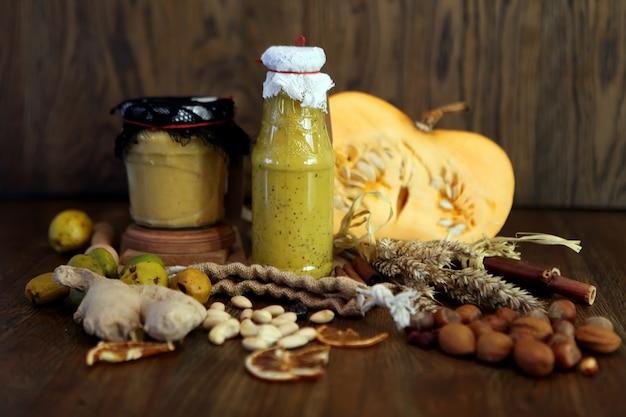 Smoothie amarelo de abóbora na garrafa bebida colorida com legumes frescos e superalimento em madeira