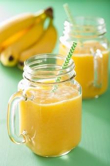Smoothie amarelo saudável com banana abacaxi manga em frascos de pedreiro