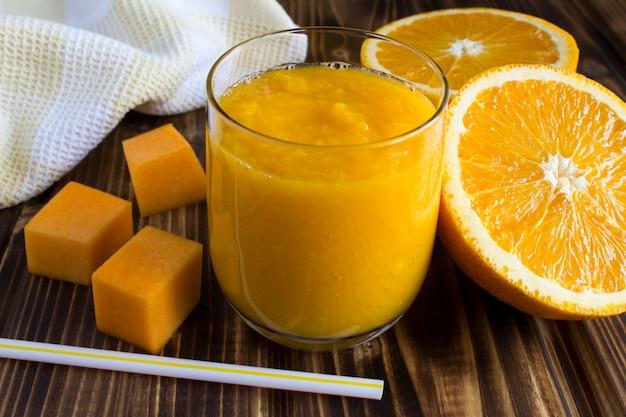 Smoothie com abóbora e laranja na superfície de madeira