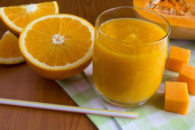 Smoothie com abóbora e laranja no guardanapo verde