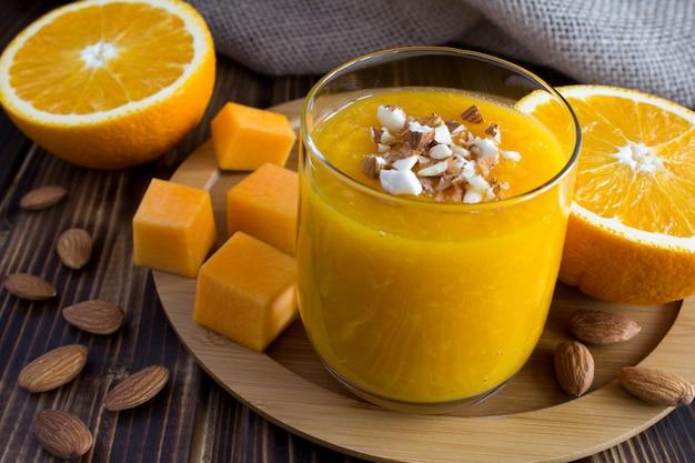 Smoothie com abóbora, laranja e amêndoa na tábua redonda de madeira