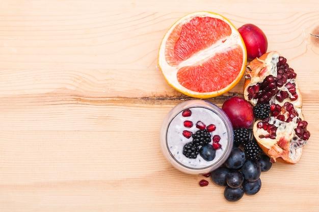 Smoothie com toranjas cortadas ao meio; ameixa; uvas; amoras e romã em pano de fundo de madeira