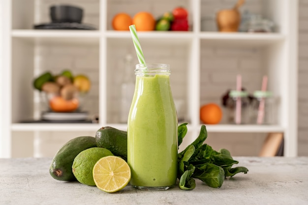 Smoothie de abacate e espinafre em vista frontal de garrafa de vidro na cozinha de casa
