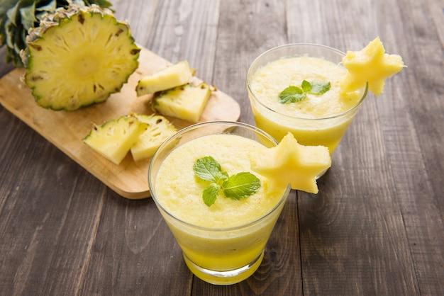 Smoothie de abacaxi com abacaxi fresco na mesa de madeira