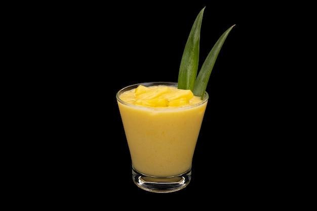 Smoothie de abacaxi e manga em um copo transparente com folhas de abacaxi e cubos de abacaxi.