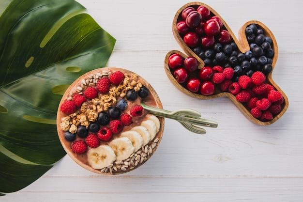 Smoothie de açaí, granola, sementes, frutas frescas em uma tigela de madeira com colher de cacto. prato cheio de bagas