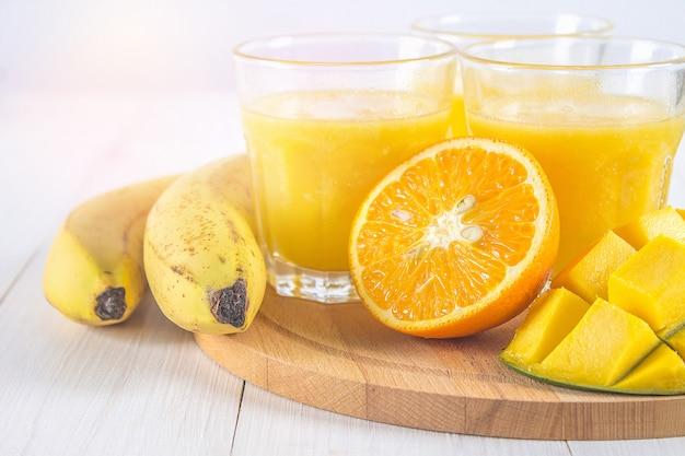 Smoothie de amarelo de manga, banana e laranja em uma mesa de madeira branca.