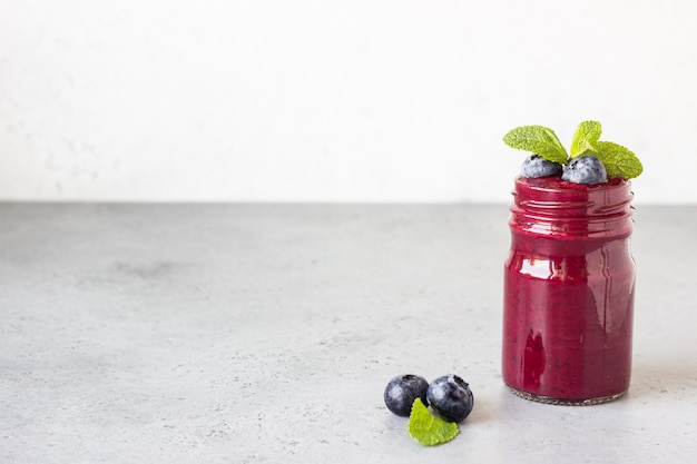 Smoothie de amora deliciosa com frutas frescas e hortelã em potes de vidro. bebida saudável de verão.
