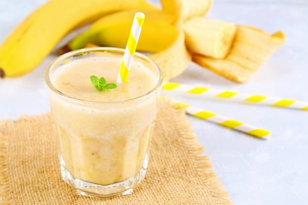 Smoothie de banana com um tubo de papel e hortelã. bananas são inteiras e cortadas em um fundo cinza.