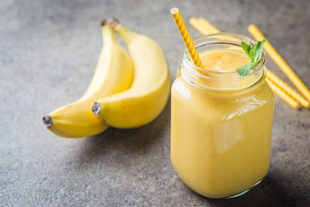 Smoothie de banana em potes de mason e frutas frescas no café da manhã saudável