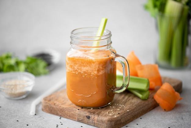 Smoothie de cenoura e aipo com sementes de gergelim em uma caneca de vidro