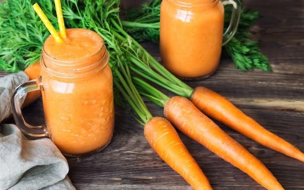 Smoothie de cenoura fresca em potes de vidro na superfície de madeira rústica.