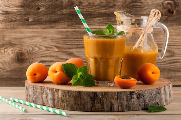 Smoothie de damasco fresco e frutas em fundo de madeira