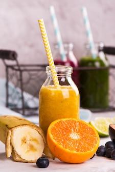 Smoothie de doce saudável amarelo em uma pequena garrafa de vidro