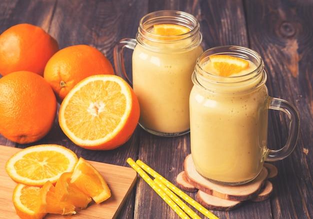 Smoothie de fruta laranja em potes de vidro com fatias de laranja frescas na superfície de madeira rústica. imagens vintage em tons.