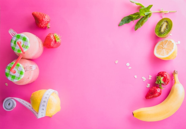 Smoothie de frutas com ingredientes em fundo rosa. conceito de alimentação saudável.