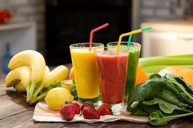 Smoothie de frutas e vegetais frescos na mesa da cozinha em vidro