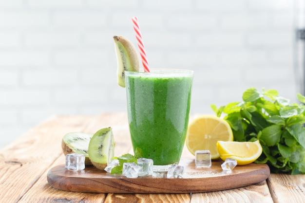 Smoothie de frutas e vegetais verde em uma mesa de madeira