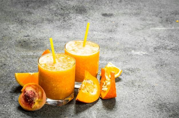 Smoothie de frutas em copos na mesa rústica.