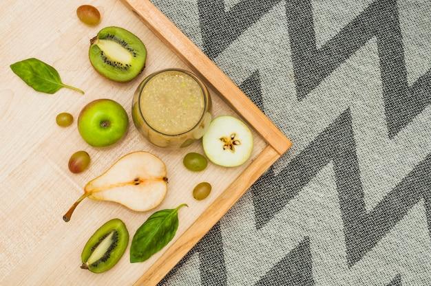 Smoothie de frutas na bandeja de madeira sobre a toalha de mesa