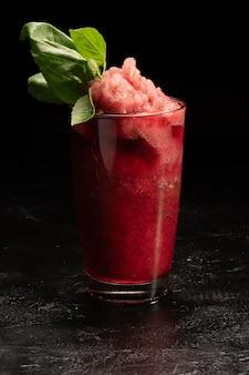 Smoothie de gelo refrescante coquetel de morango e manjericão em um copo de vidro transparente.
