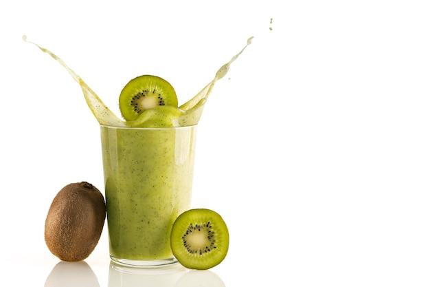 Smoothie de kiwi delicioso e nutritivo em fundo branco. fatias de kiwi caindo no respingo. bebida nutritiva natural para um estilo de vida saudável. bebida orgânica e vitamínica. espaço para texto.