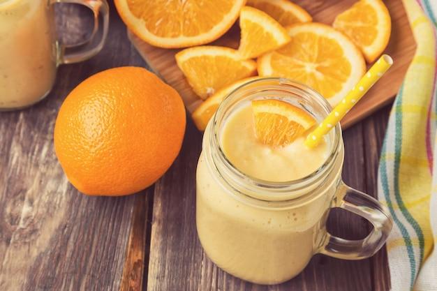 Smoothie de laranja em uma jarra de vidro com fatias de laranja fresca em uma superfície de madeira rústica