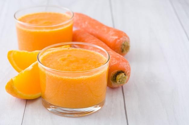 Smoothie de laranja, maçã e cenoura na mesa de madeira branca