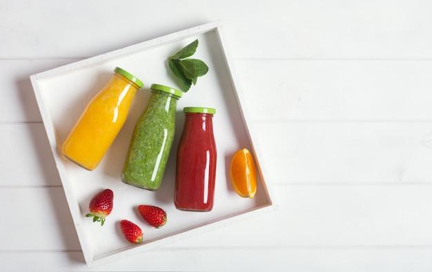 Smoothie de laranja, morango e brócolis fresco em garrafas com frutas e hortelã em uma caixa rústica de madeira branca