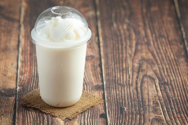 Smoothie de leite de coco em uma mesa de madeira
