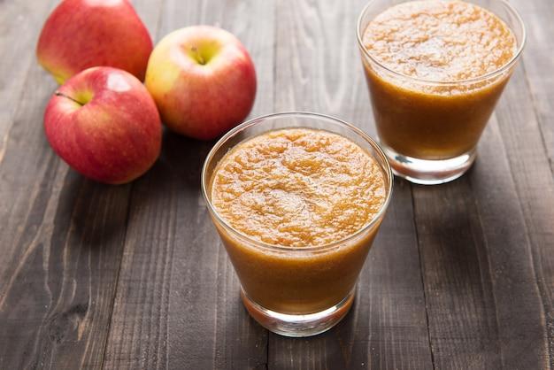 Smoothie de maçãs vermelhas flash na mesa de madeira