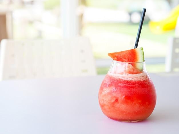 Smoothie de melancia com fatia de fruta e palha no fundo da mesa branca.