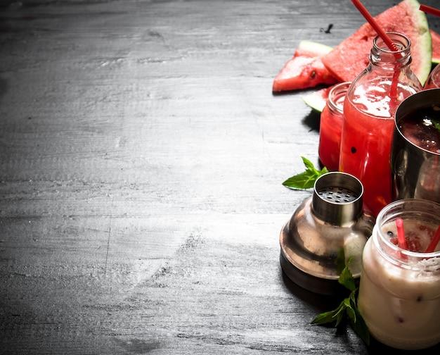Smoothie de melancia com suco e hortelã-pimenta. em uma mesa de madeira preta.