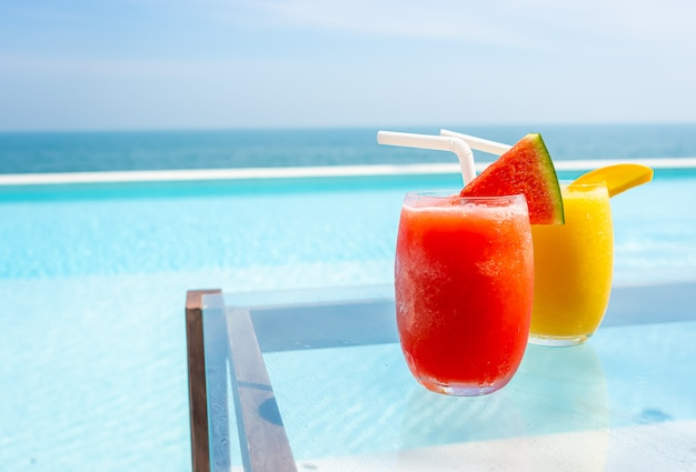 Smoothie de melancia e smoothie de manga com piscina e mar