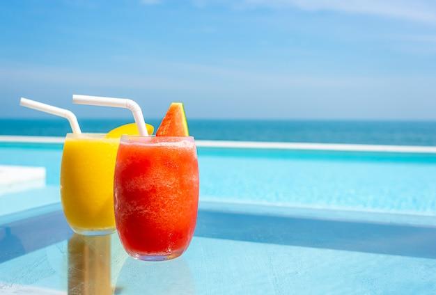 Smoothie de melancia e smoothie de manga na piscina