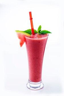 Smoothie de melancia em um copo alto com hortelã no fundo branco.