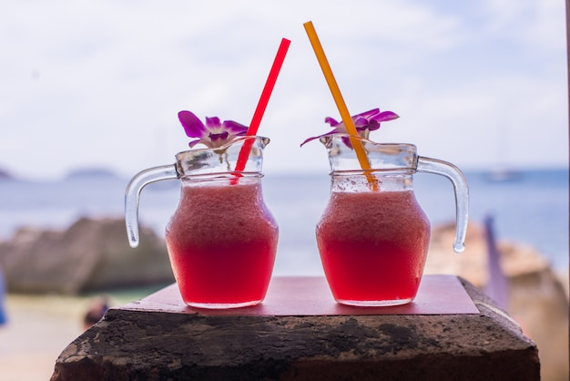 Smoothie de melancia em vidro com melancia e flor na praia