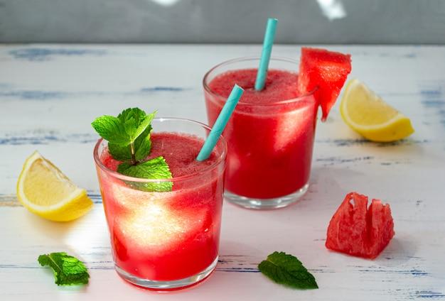 Smoothie de melancia frio com hortelã e limão em copos. um coquetel de suco de melancia