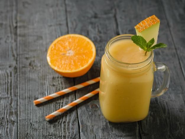 Smoothie de melão, laranja e banana recém-feitos e dois canudos de coquetel em uma mesa de madeira