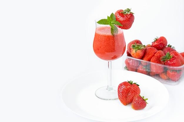 Smoothie de morango em um copo com uma perna alta, decorado com morangos e hortelã em branco