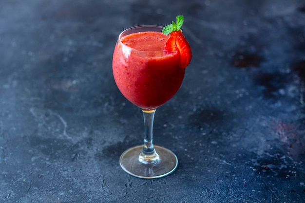 Smoothie de morango gelado fresco no copo de vinho decorado com uma fatia de morango e hortelã em um fundo escuro. bebida de verão pegajosa.