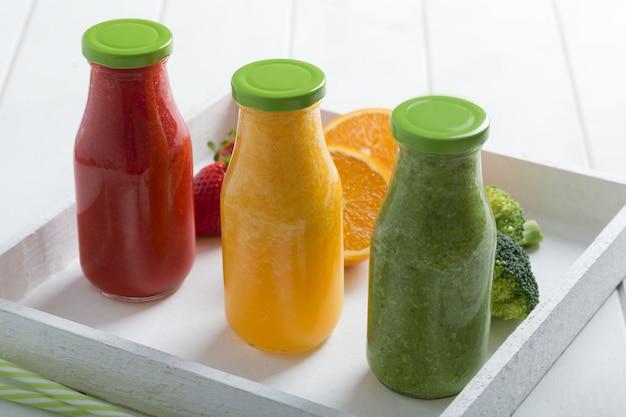 Smoothie de morango, laranja e brócolis fresco em três garrafas com frutas e legumes
