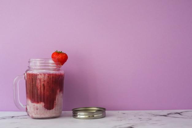 Smoothie de morango no pote contra fundo rosa