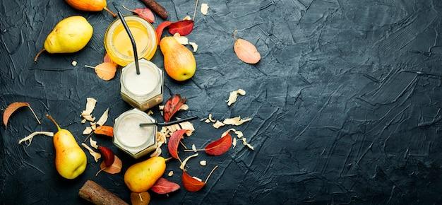 Smoothie de pera e gengibre e folhas caídas. jarra de smoothies de frutas. copie o espaço